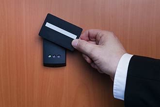 business man swiping a card in front of an access control card reader